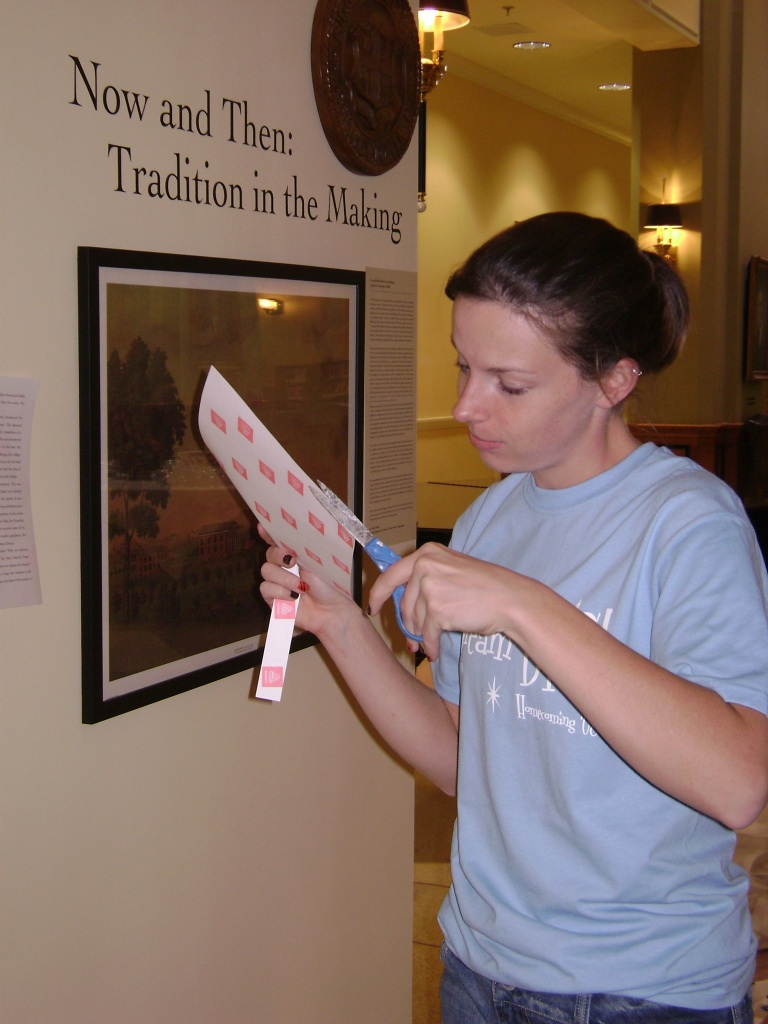 Chelsey cuts labels for the walls of the Cochenour Gallery.